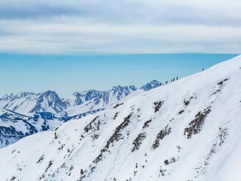 Esquiando cuesta arriba durante una carrera de esquí de larga distancia en Shedhorn Skimo en Big Sky, Montana