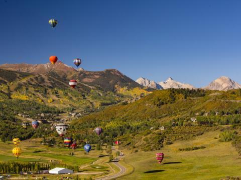 Globos aerostáticos flotando sobre el paisaje durante el Snowmass Balloon Festival en Colorado